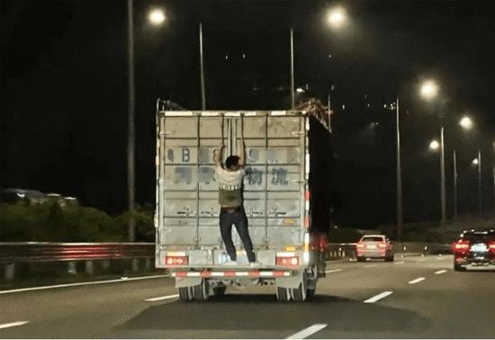惊呆!深圳高速路上一男子扒在疾驰的货车厢门上